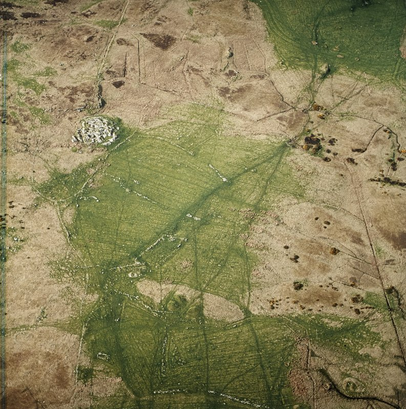Oblique aerial view centred on the remains of the farmstead and field system with dun, settlement and burnt mounds adjacent, taken from the SSE.