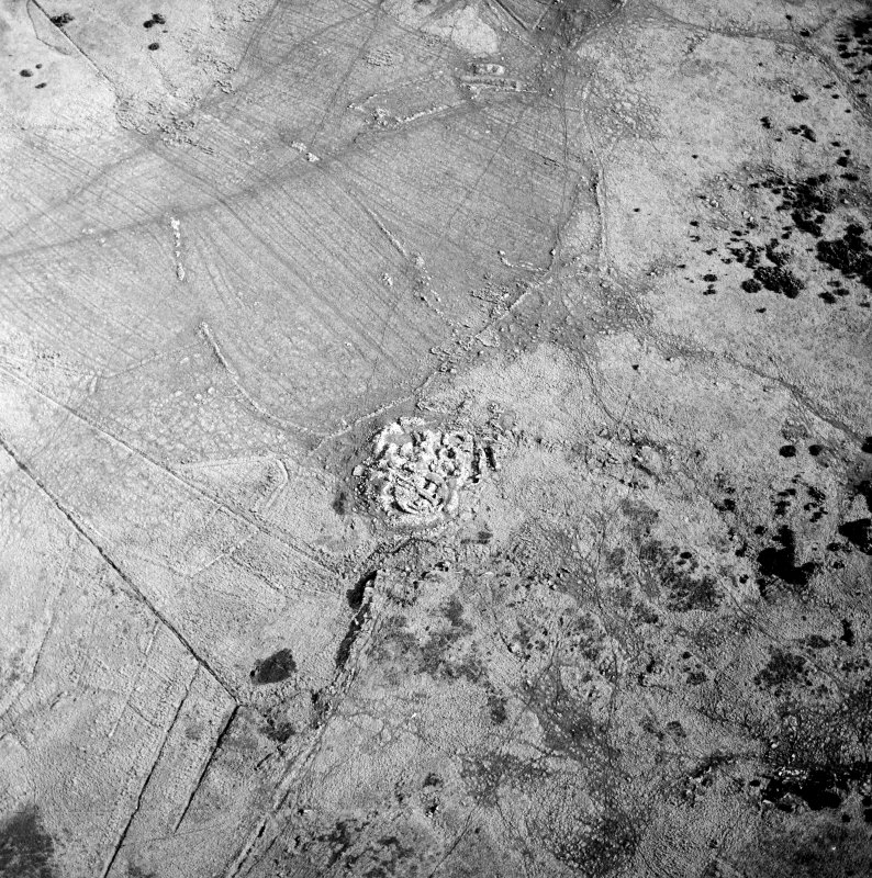 Oblique aerial view centred on the remains of the dun, settlement and field system with hut-circle and farmstead adjacent, taken from the NNW.