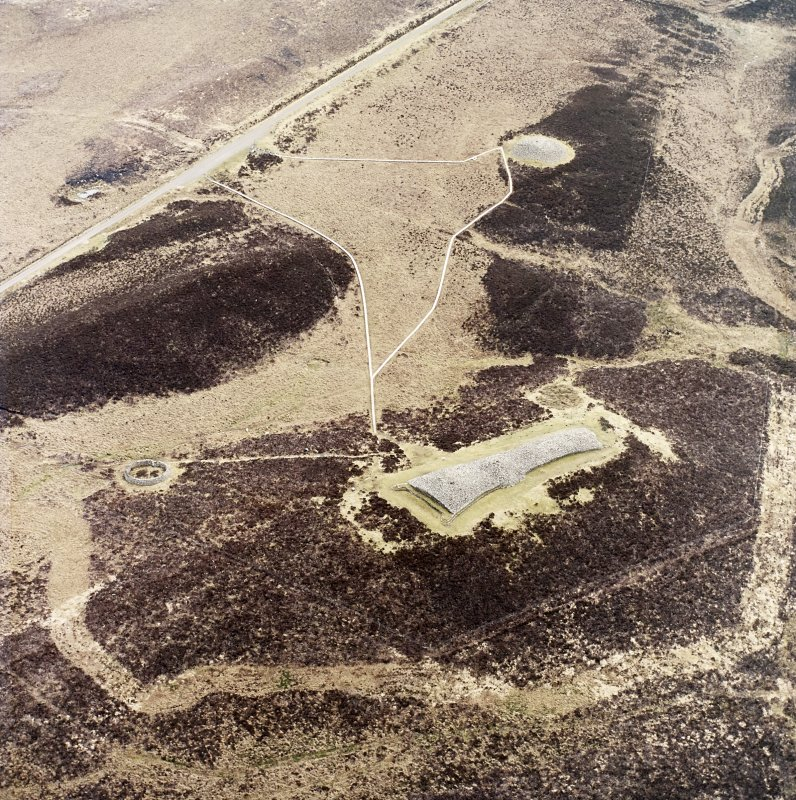 Oblique aerial view centred on the remains of the chambered  cairns, taken from the NW.