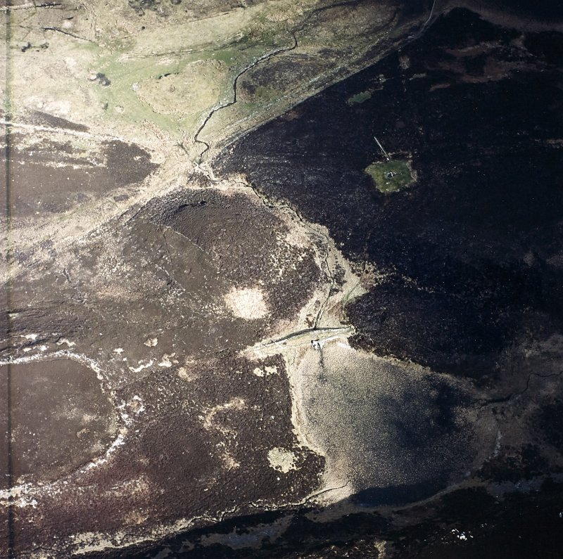 Oblique aerial view centred on the remains of the dam with the fort and chambered cairn adjacent, taken from the WNW.