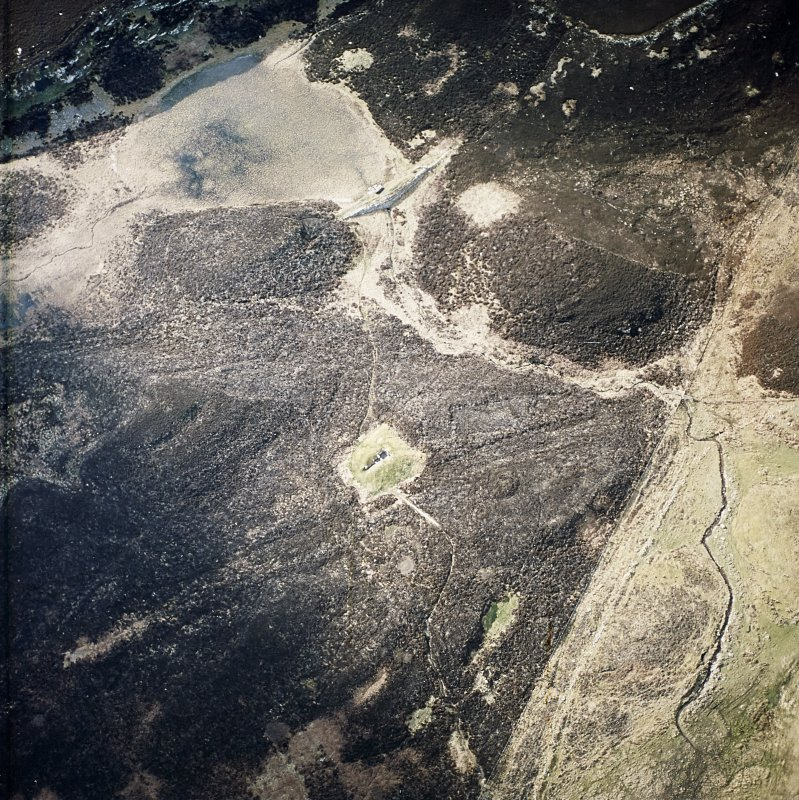 Oblique aerial view centred the remains of the chambered cairn and the dam, taken from the SE.