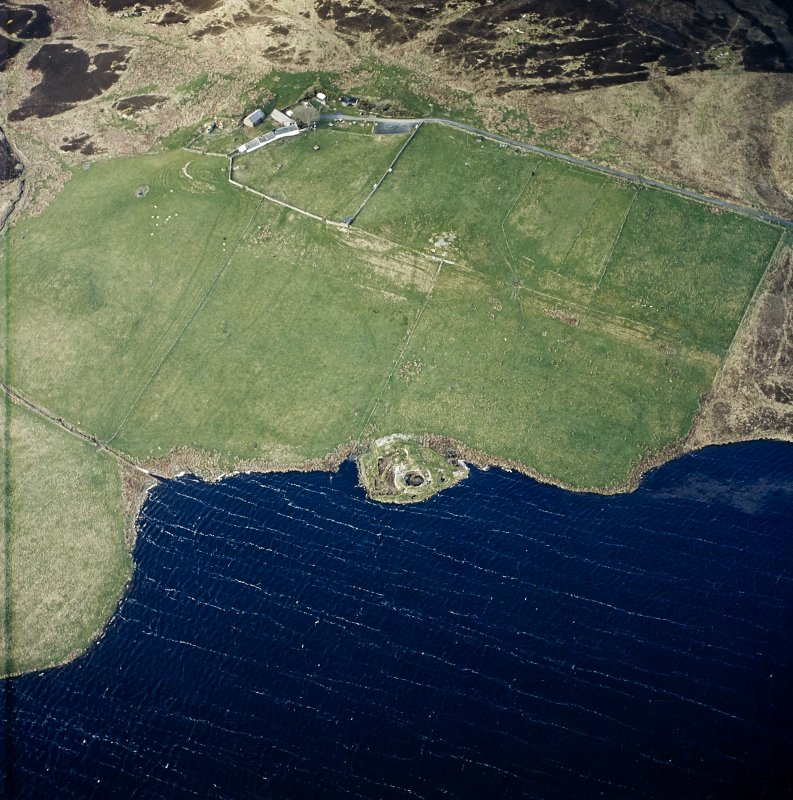 Oblique aerial view centred on the remains of the broch with farmstead adjacent, taken from the NE.