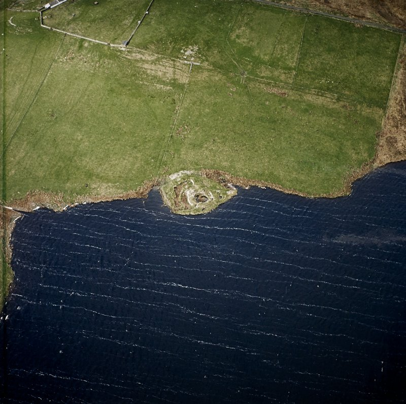 Oblique aerial view centred on the remains of the broch, taken from the ENE.