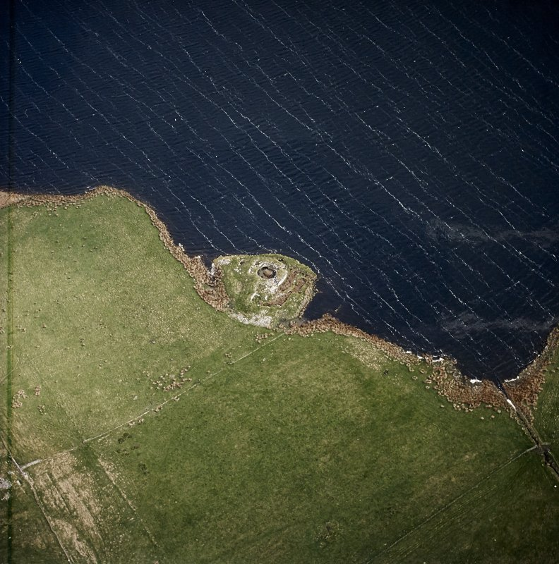 Oblique aerial view centred on the remains of the broch, taken from the SSW.