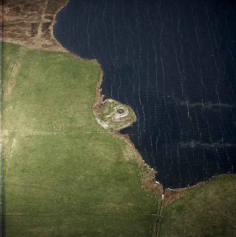 Oblique aerial view centred on the remains of the broch, taken from the SSE.