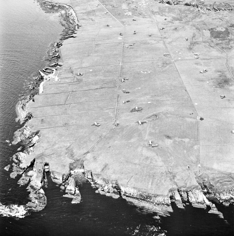 Stroma, oblique aerial view, taken from the E, centred on Uppertown township. A dovecot and burial ground, and the remains of Fendie Clett castle are visible in the bottom left-hand corner of the photograph.