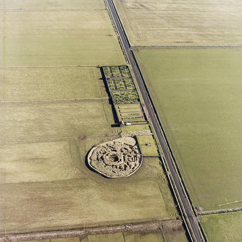 Oblique aerial view centred on the remains of the broch with the memorial and graveyard adjacent, taken from the SW.
