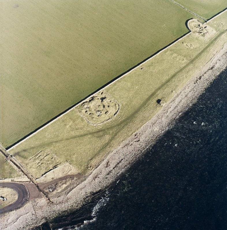 Oblique aerial view of the remains of the brochs, buildings, possible building, pillbox and slipway, taken from the S.