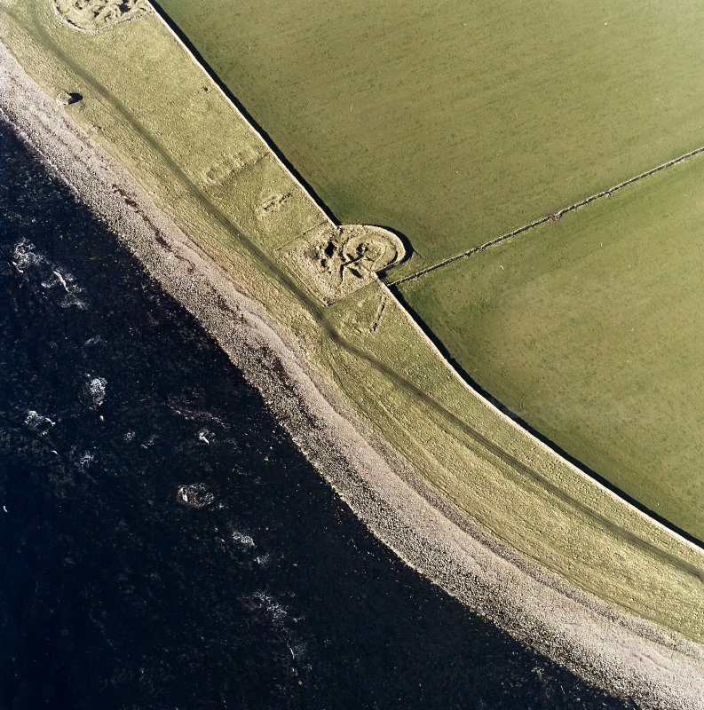 Oblique aerial view centred on the remains of the broch with the possible building and pillbox adjacent, taken from the ENE.