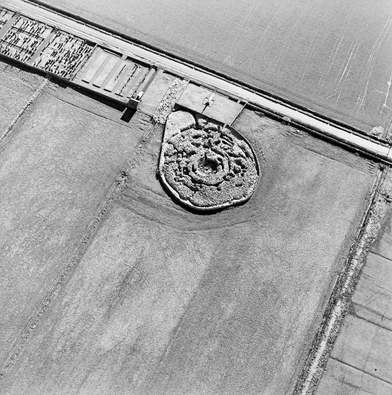 Oblique aerial view centred on the remains of the broch with the memorial and graveyard adjacent, taken from the NW.