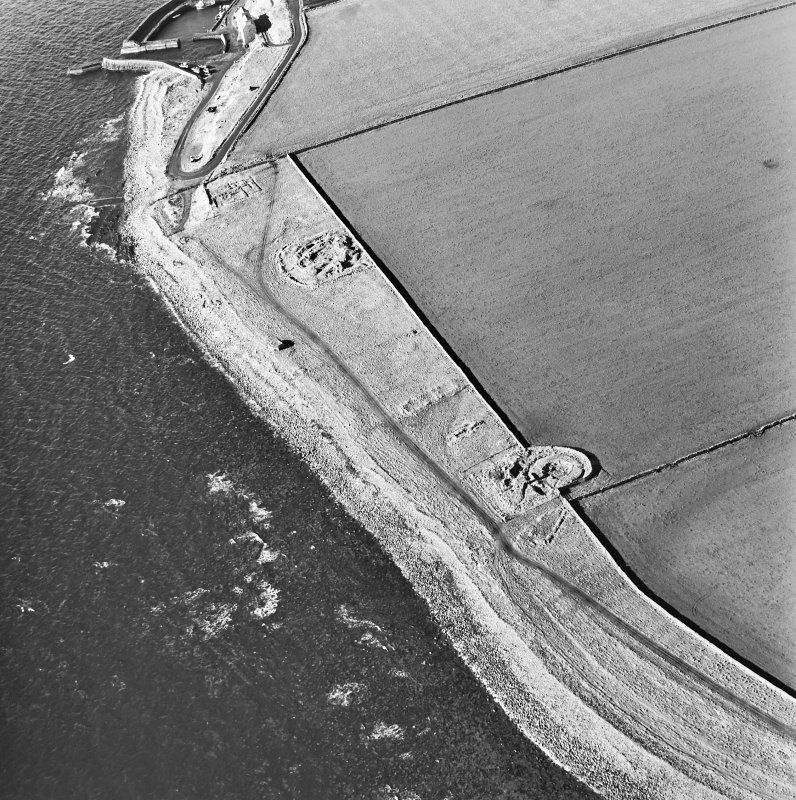 Oblique aerial view of the remains of the brochs, buildings, possible building, pillbox and slipway, taken from the E.