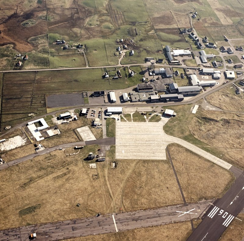 Oblique aerial view centred on the village with the airfield adjacent, taken from the NNE.