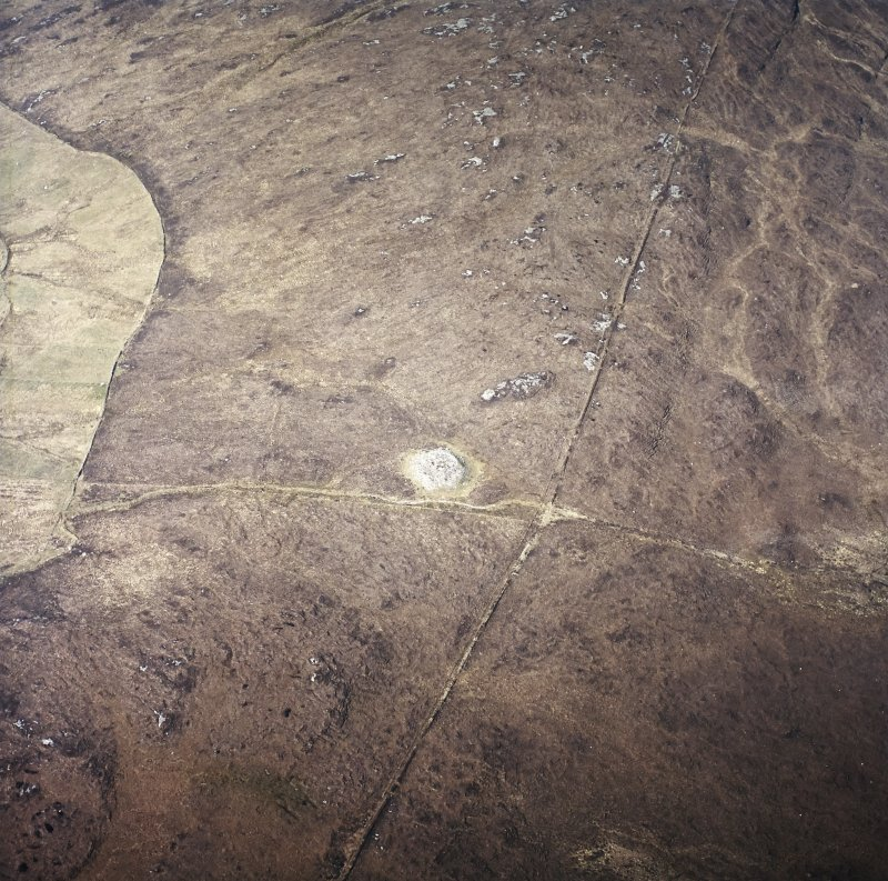 Oblique aerial view centred on the remains of the chambered cairn, taken from the E.