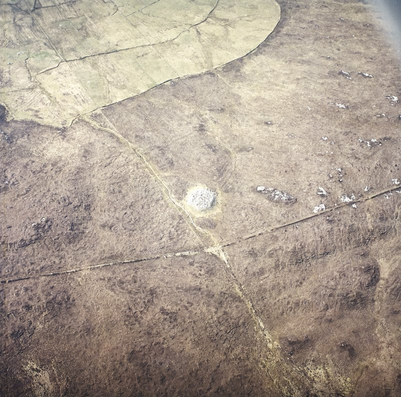 Oblique aerial view centred on the remains of the chambered cairn, taken from the NE.