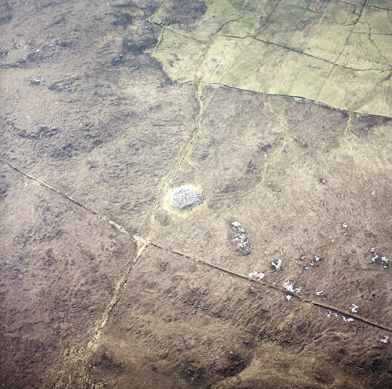 Oblique aerial view centred on the remains of the chambered cairn, taken from the NNW.