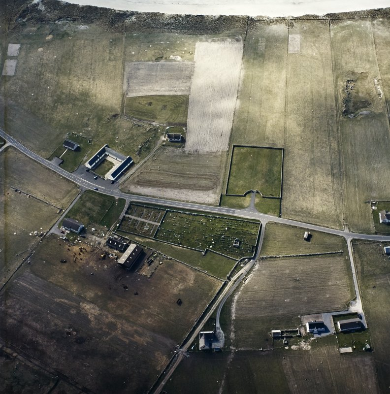Oblique aerial view centred on the remains of the chapel and the burial enclosure, with the farmstead and the farmsteading adjacent, taken from the E