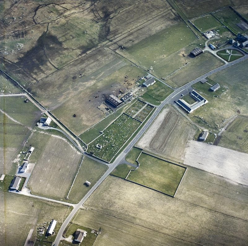Oblique aerial view centred on the remains of the chapel and the burial enclosure, with the farmsteads and the farmsteadings adjacent, taken from the N