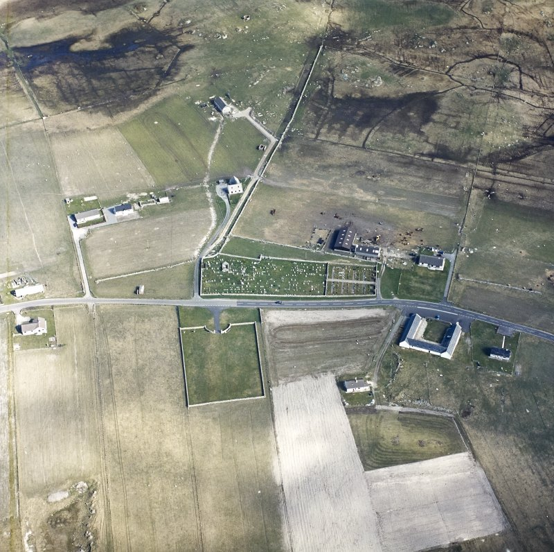 Oblique aerial view centred on the remains of the chapel and the burial enclosure, with the farmstead and the farmsteading adjacent, taken from the NW