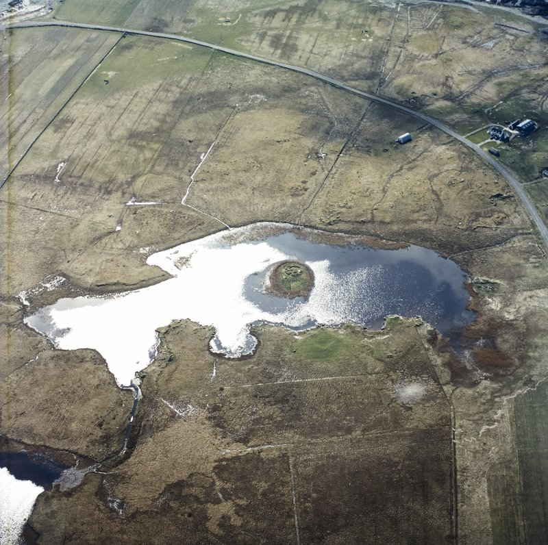 Oblique aerial view centred on the remains of the dun, taken from the NE.