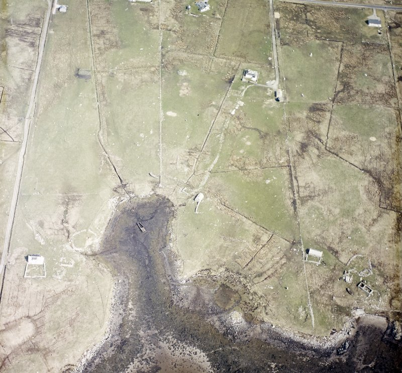 Oblique aerial view centred on the remains of the buildings with the remains of the chambered cairn and standing stone adjacent, taken from the SW.