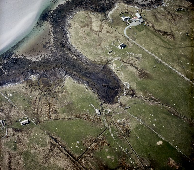 Oblique aerial view centred on the remains of the buildings with the remains of the chambered cairn and standing stone adjacent, taken from the ESE.