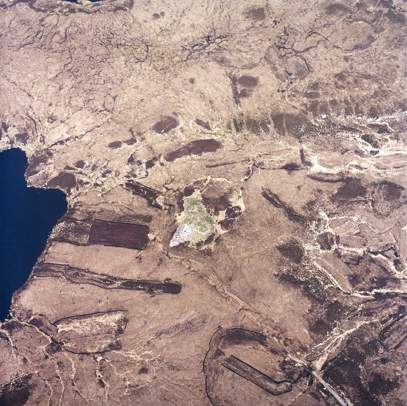 Oblique aerial view centred on the remains of the chambered cairn, taken from the SW.