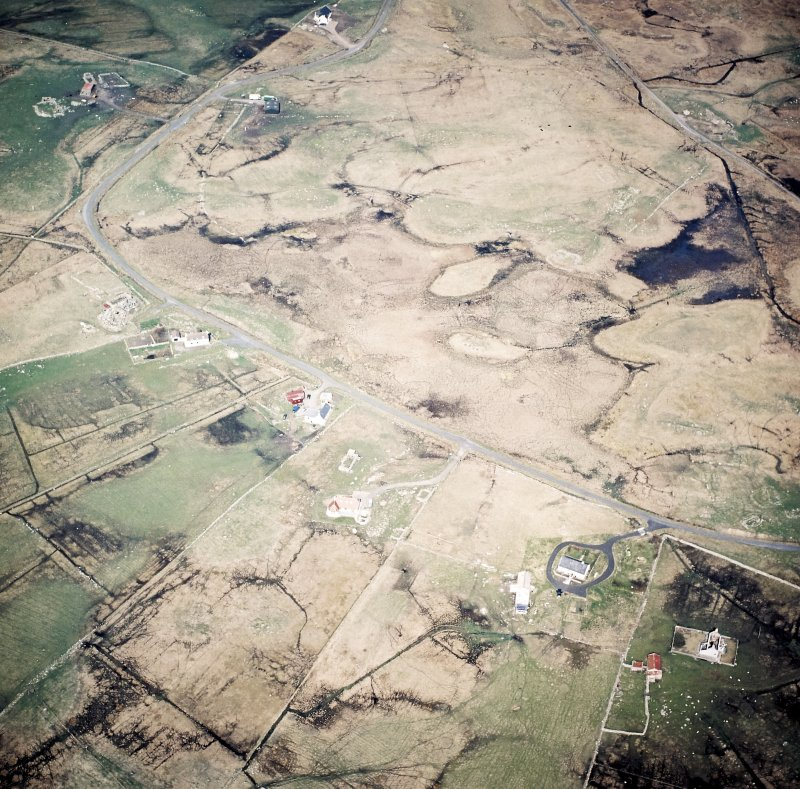 Oblique aerial view centred on the crofting township and the remains of the buildings, taken from the S.