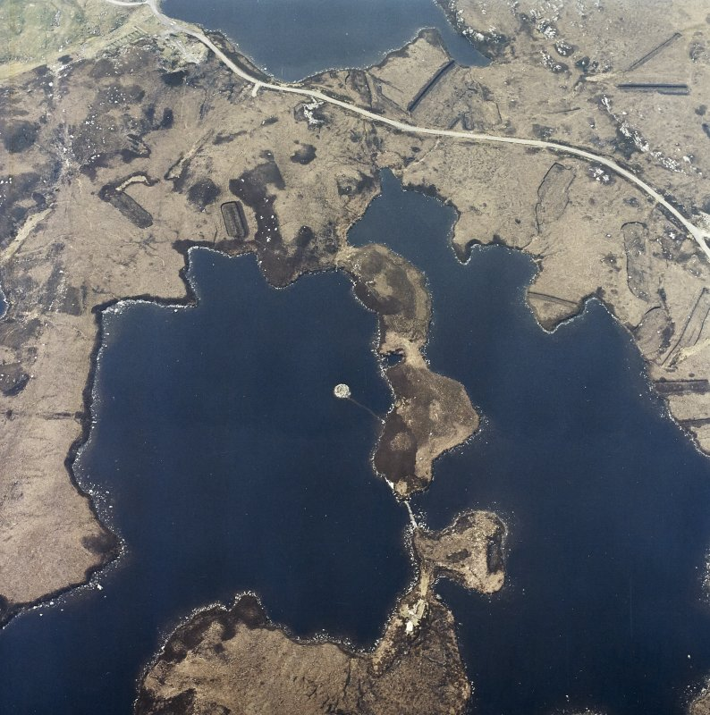 Oblique aerial view centred on the remains of the dun, taken from the E.
