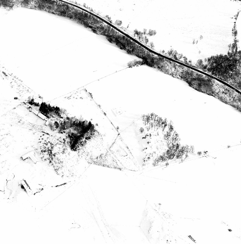 Oblique aerial view of Carn Daley centred on the remains of a chambered cairn with a township adjacent, taken from the W.
