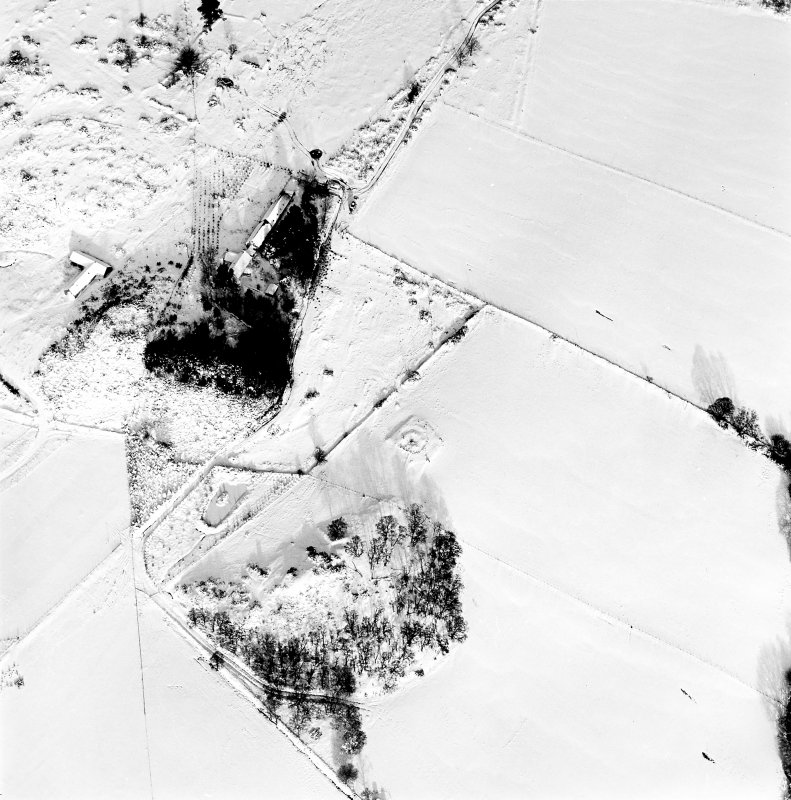 Oblique aerial view of Carn Daley centred on the remains of a chambered cairn with a township adjacent, taken from the S.