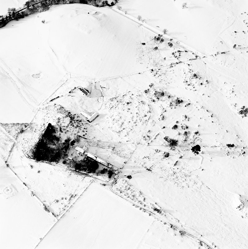 Oblique aerial view of Carn Daley centred on the remains of a chambered cairn with a township adjacent, taken from the E.