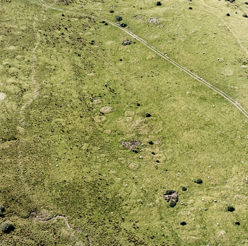 Oblique aerial view of Garbeg centred on the remains of square and round barrows in an area of hut-circles, small cairns and a field-system, taken from the NE.