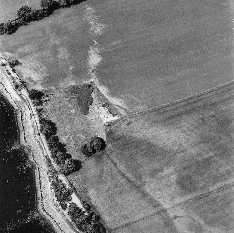 Coulmore, oblique aerial view, taken from the SE, centred on the remains of a possible castle and the cropmarks of an enclosure and rig.