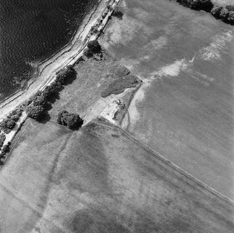 Coulmore, oblique aerial view, taken from the ESE, centred on the remains of a possible castle and the cropmarks of an enclosure and rig.