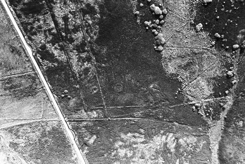 Oblique aerial view centred on the remains of the hut-circles, taken from the WNW.