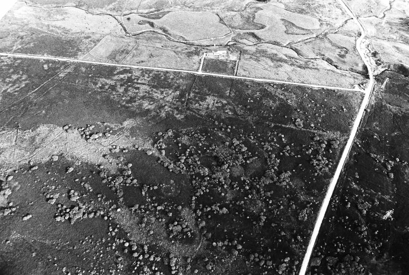 General oblique aerial view centred on the remains of the sheepfold and the hut-circles, taken from the NNW.