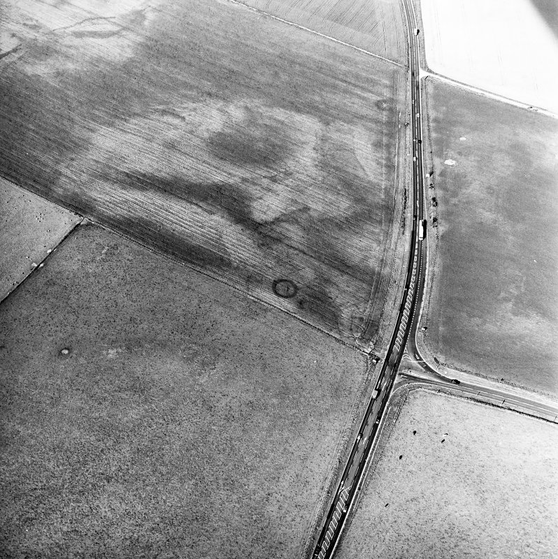 Newton and Upper Cullernie, oblique aerial view, taken from the SE, centred on the cropmarks of a barrow. A ring-ditch is visible as a cropmark in the top centre of the photograph.