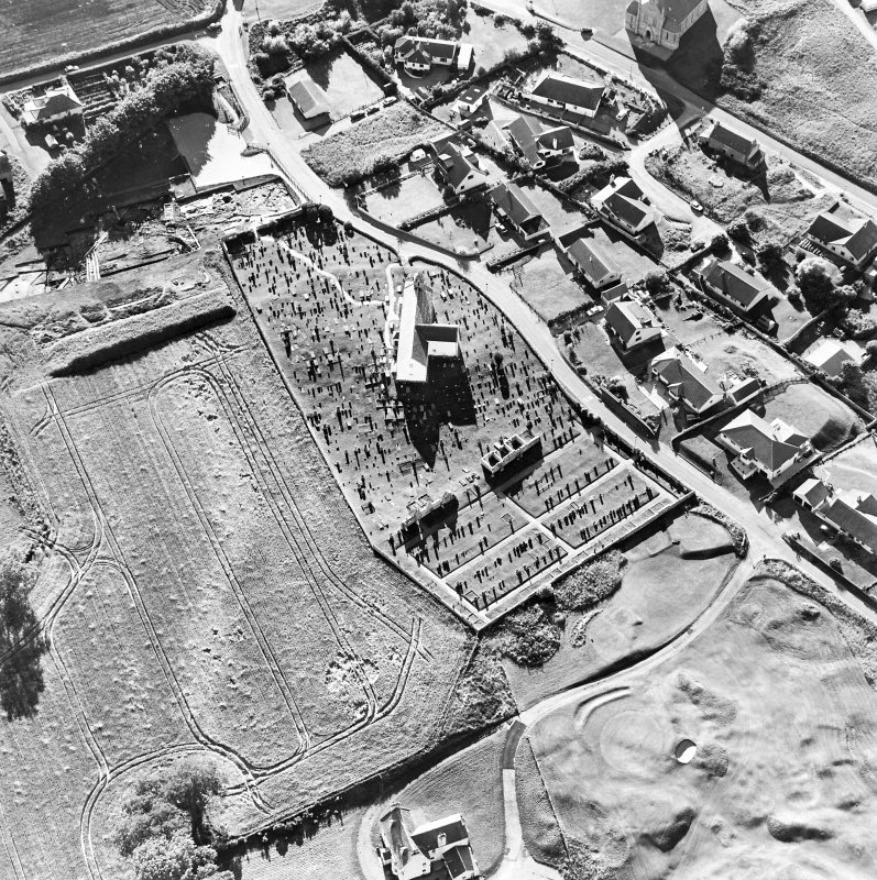 Oblique aerial view centred on the church and churchyard with excavation adjacent, taken from the E.