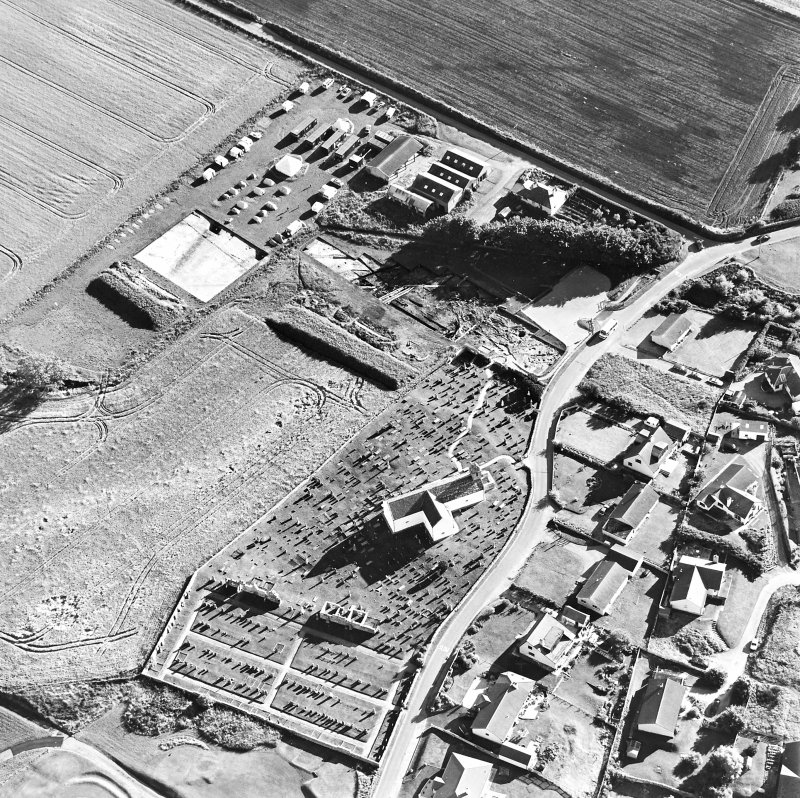 Oblique aerial view centred on the church and churchyard with excavation adjacent, taken from the NNE.