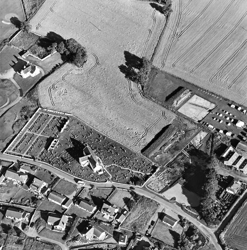 Oblique aerial view centred on the church, churchyard and excavation, taken from the WNW.