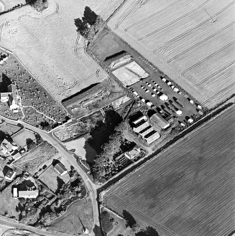 Oblique aerial view centred on the excavation with church and churchyard adjacent, taken from the W.