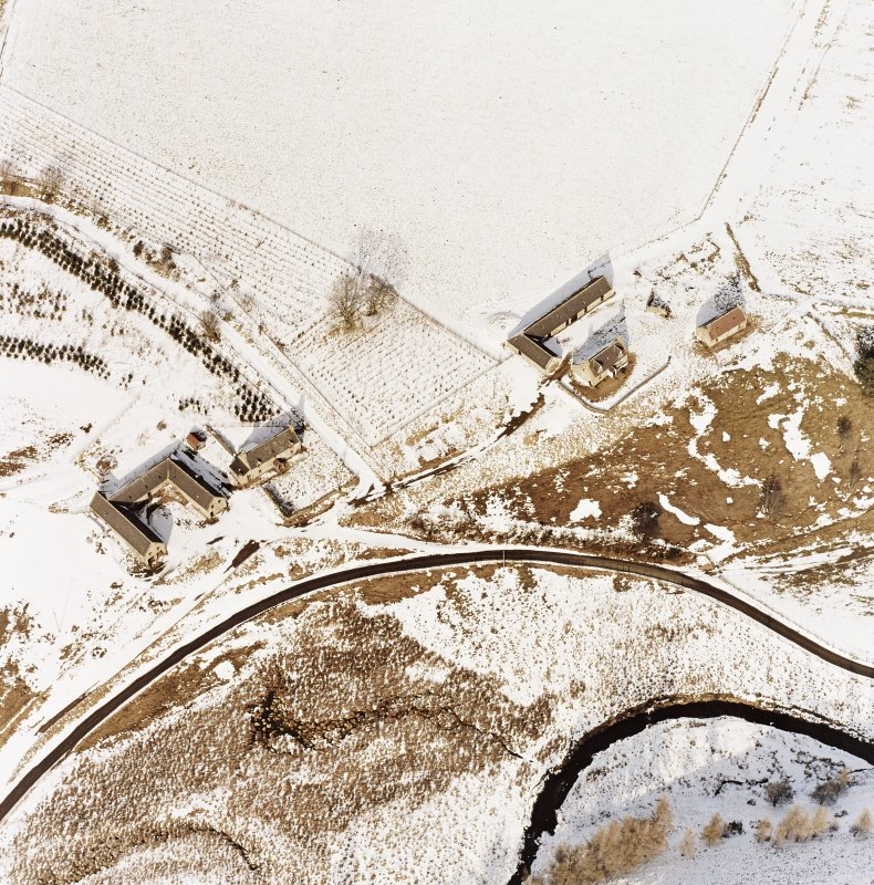 Badenyon, oblique aerial view, taken from the SW, showing the site of Badenyon Castle and the farmsteading in the top left-hand corner area of the photograph.