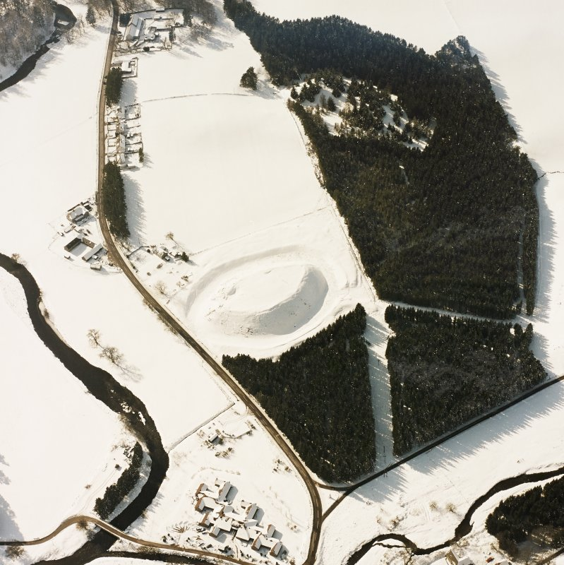 Oblique aerial view of Doune of Invernochty centred on the remains of the motte, chapel, castle, building and observation post, taken from the NE.