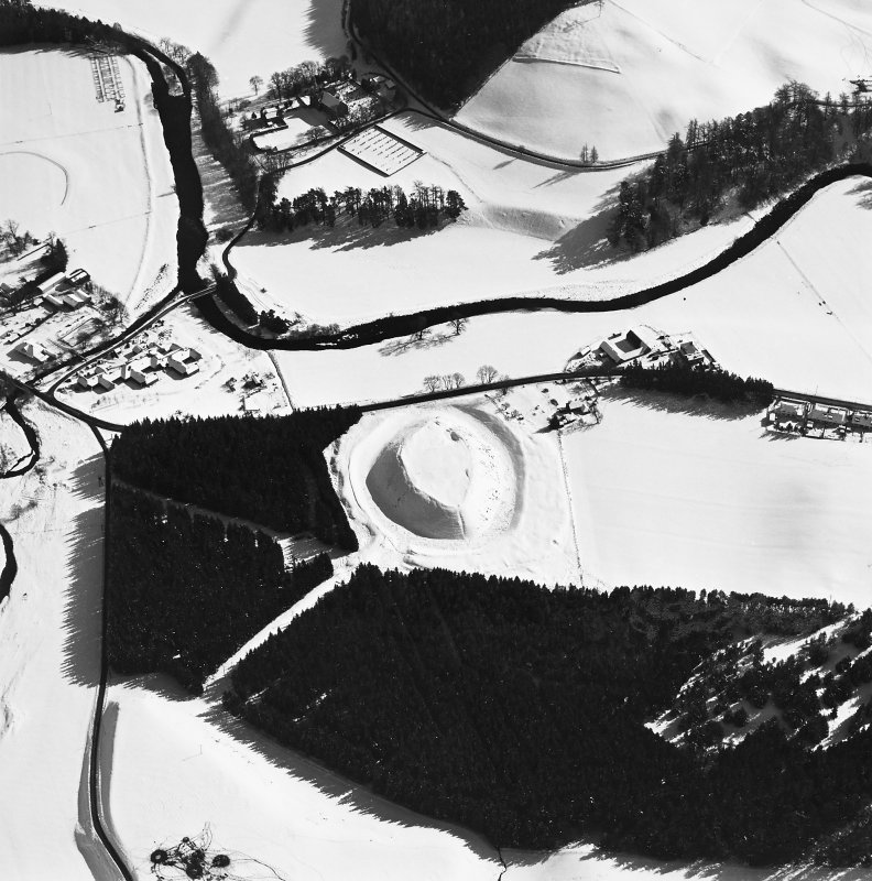 Oblique aerial view of Doune of Invernochty centred on the remains of the motte, chapel, castle, building and observation post with Bellabeg and Strathdon Parish Church adjacent, taken from the NW.