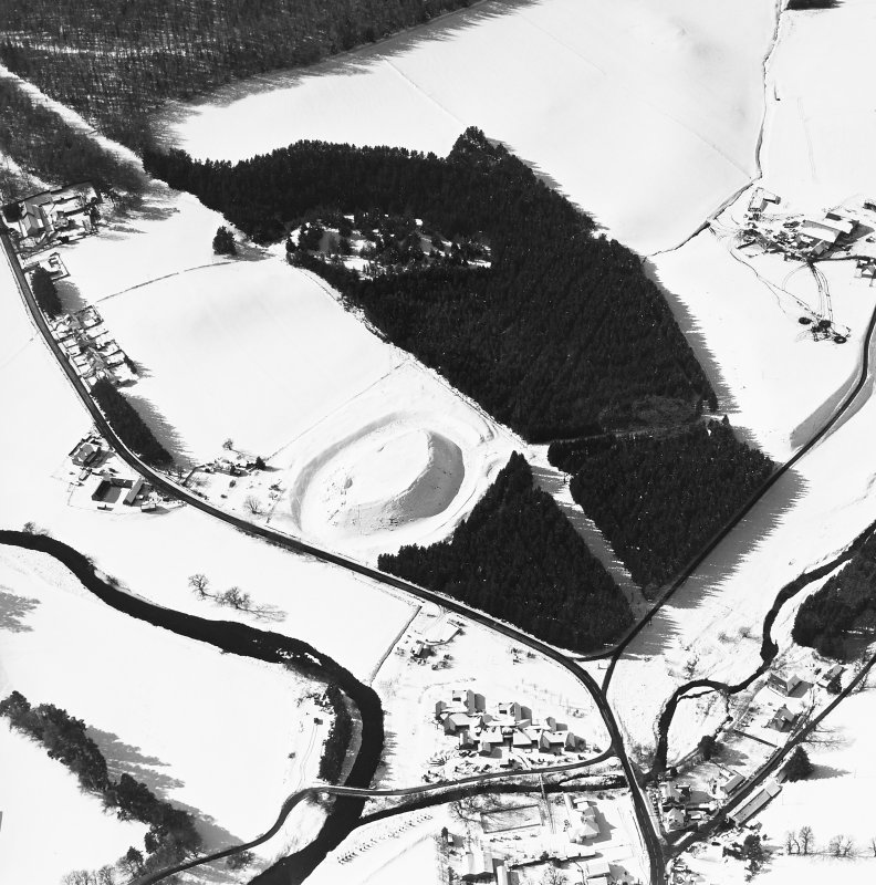 Oblique aerial view of Doune of Invernochty centred on the remains of the motte, chapel, castle, building and observation post with Bellabeg adjacent, taken from the ENE.