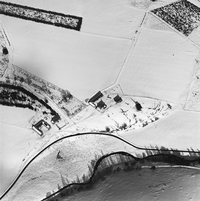 Oblique aerial view of Badenyon centred on the site of the castle, the remains of a limekiln, and a farmsteading, taken from the SSW.