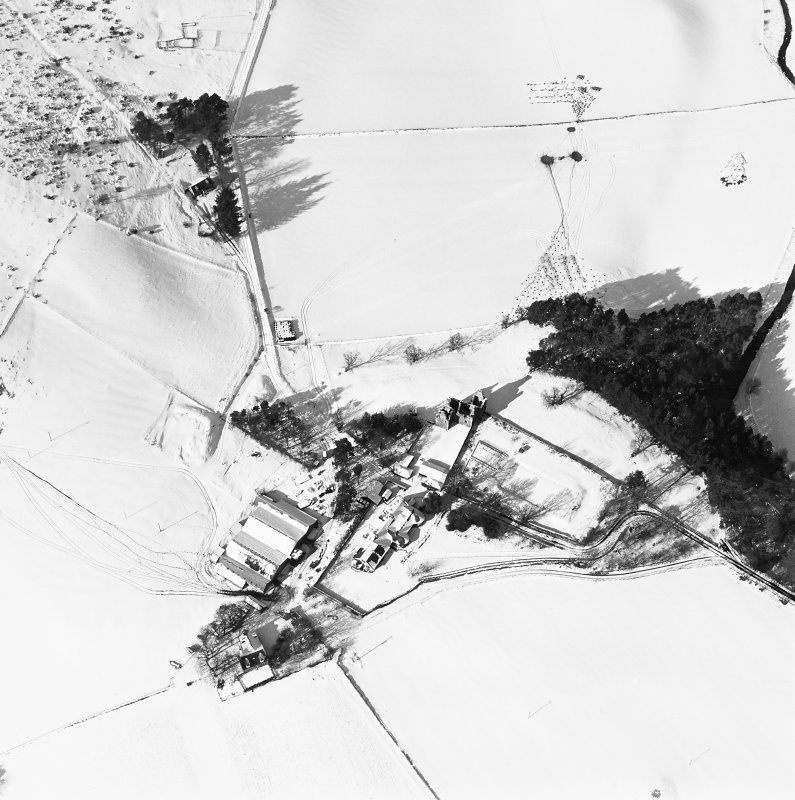 Oblique aerial view of Glenbuchat House centred on the country house, walled garden, farmsteading, cottage and the remains of a castle, taken from the SE.