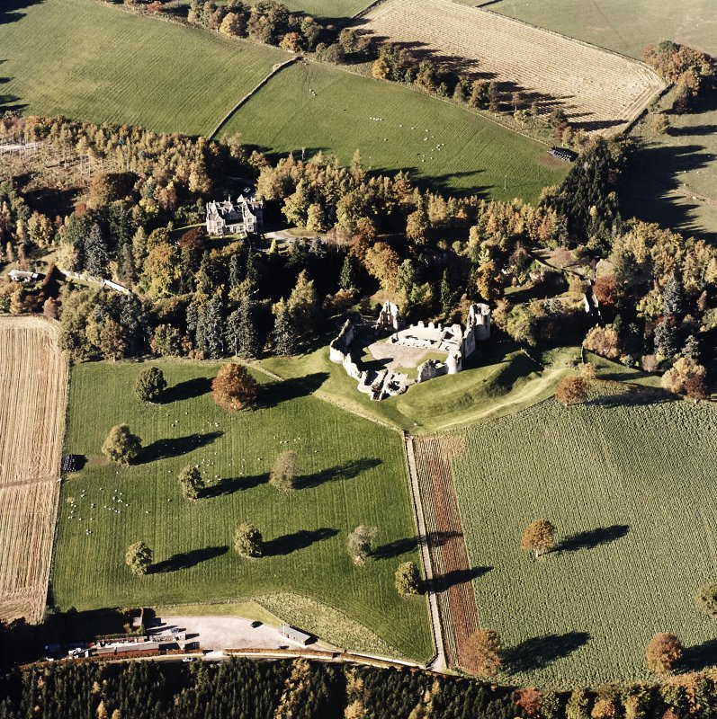 Oblique aerial view of Kildrummy castle centred on the remains of the castle with hotel adjacent, taken from the SE.