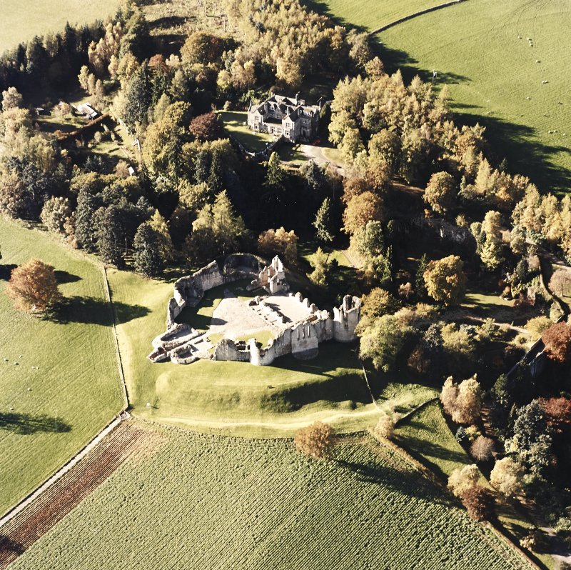 Oblique aerial view of Kildrummy castle centred on the remains of the castle, with hotel adjacent taken from the E.