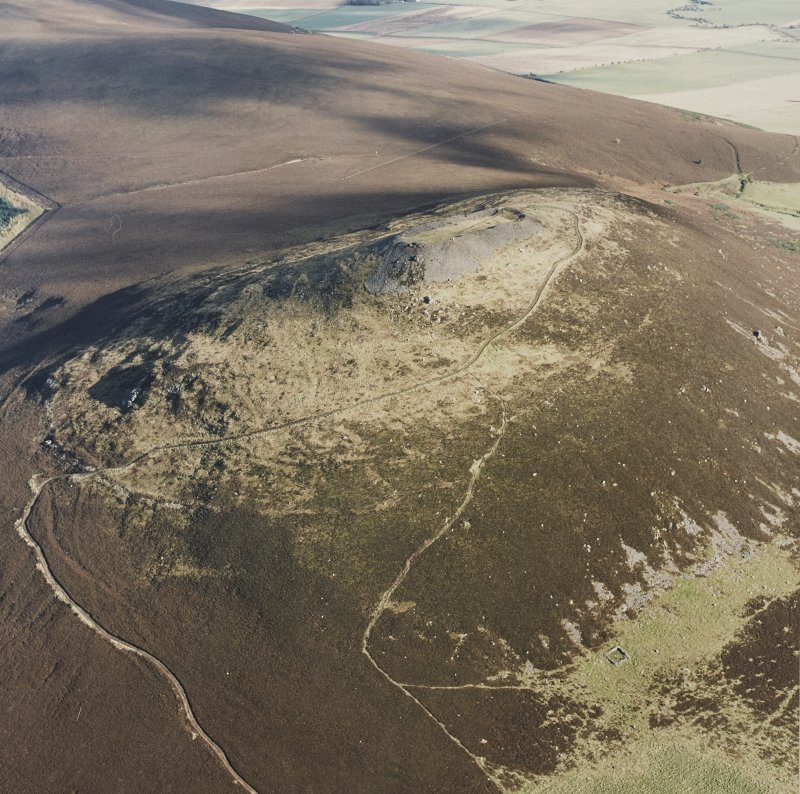 Oblique aerial view of Tap o' Noth centred on the fort, taken from the SW.